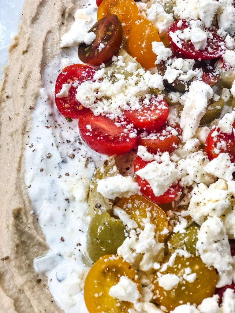 Tomatoes on top of greek layer dip
