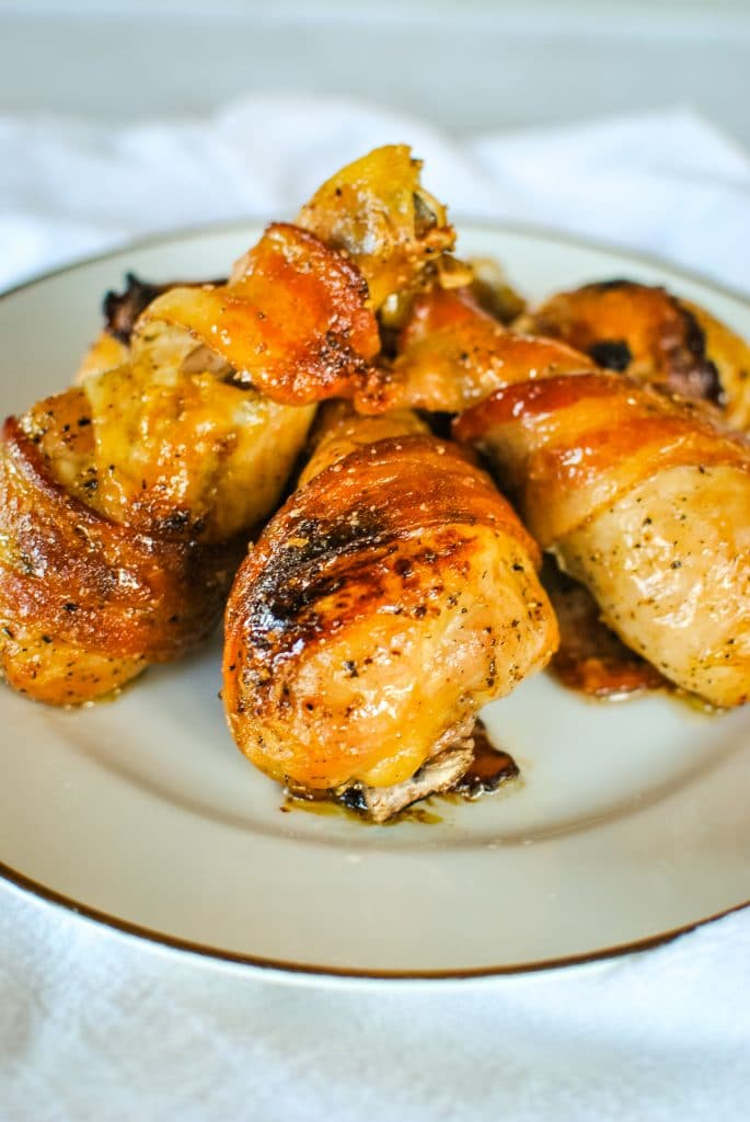 Bacon-Wrapped Chicken Legs are *exactly* what you want! Juicy chicken legs are wrapped in bacon, then slathered with a honey Cholula sauce.