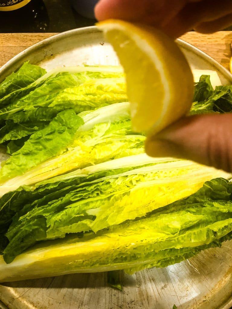 squeezing lemon over romaine lettuce