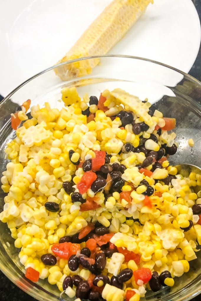 Mixing Corn into black bean salad