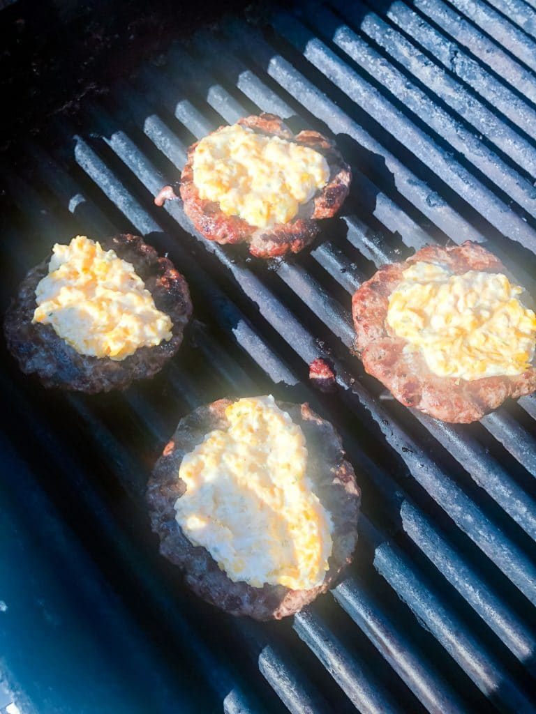 topping grilled burgers with cheese